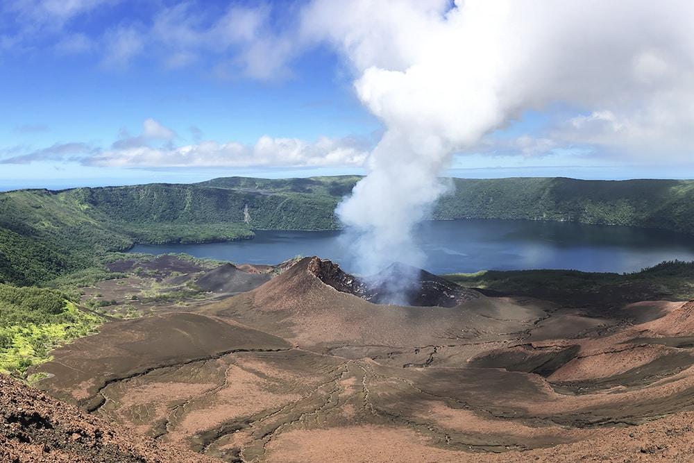 A volcano spews smokes