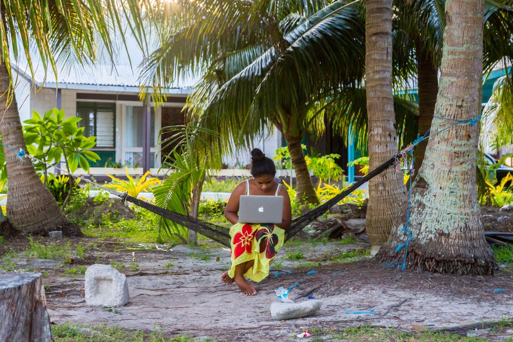 A woman uses a laptop in Tuvalu