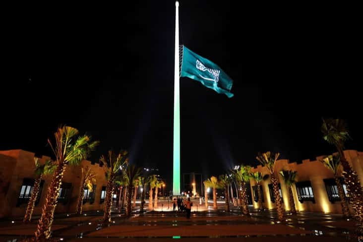 The Saudi flag being hoisted onto the tallest flagpole in the world at night