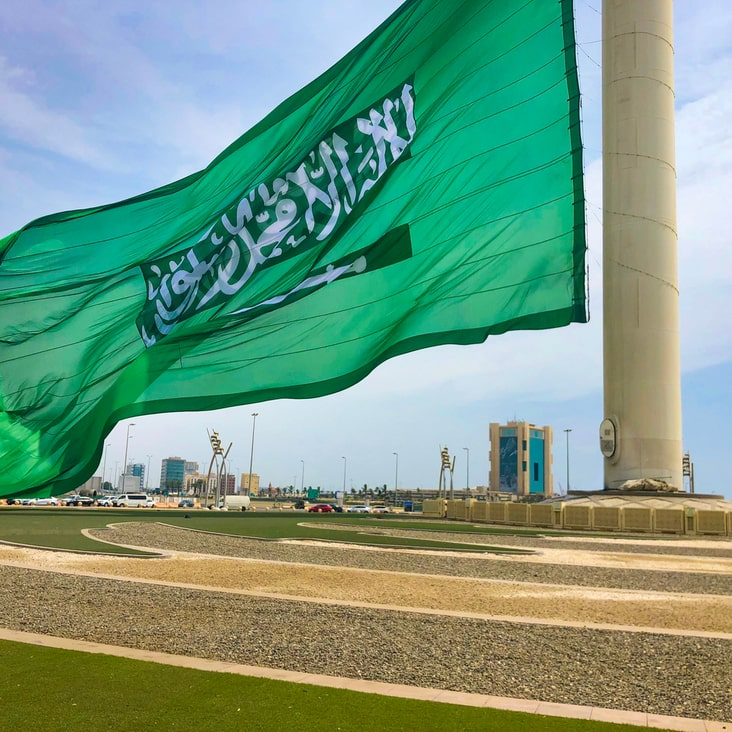 The Saudi flag being attached at the flagpole's base