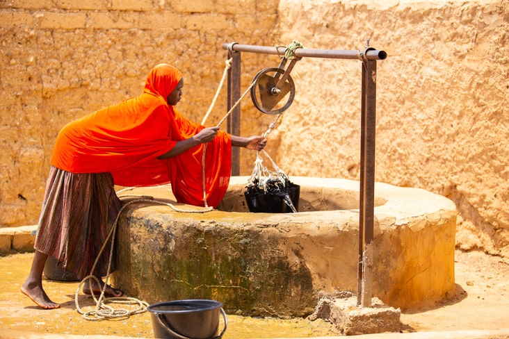 A woman takes water from a well