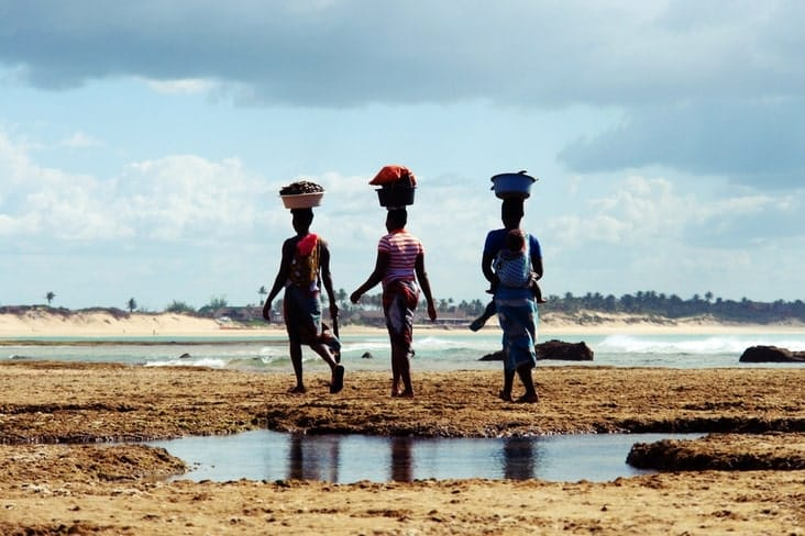 Mozambican women carry baskets on their heads