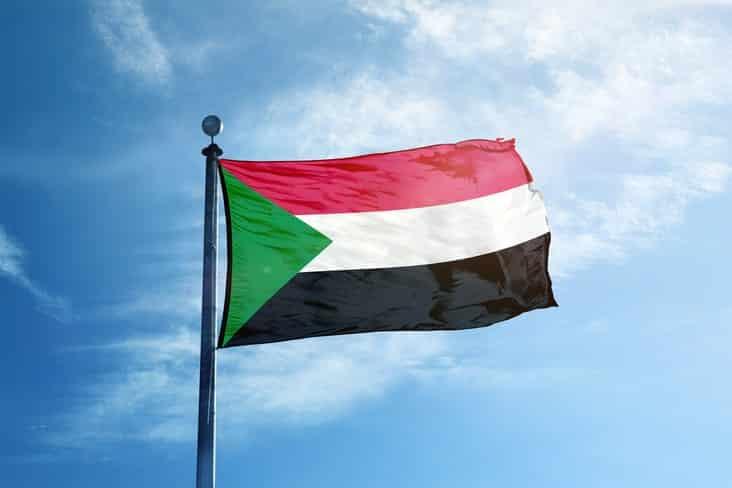 Sudan's flag flying in front of blue sky