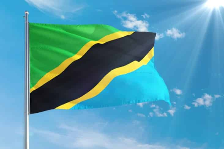 The flag of Tanzania flying in front of a blue sky