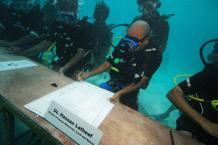 Members of the government underwater signing papers at a desk